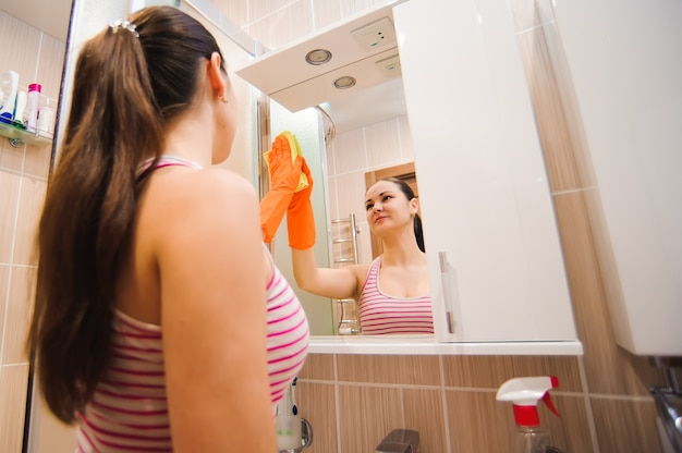 Brunette cleans mirror with help of yellow cloth and special mean of cleaning.
