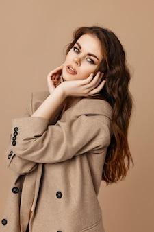 Brunette in coat fashion glamor home beige background
