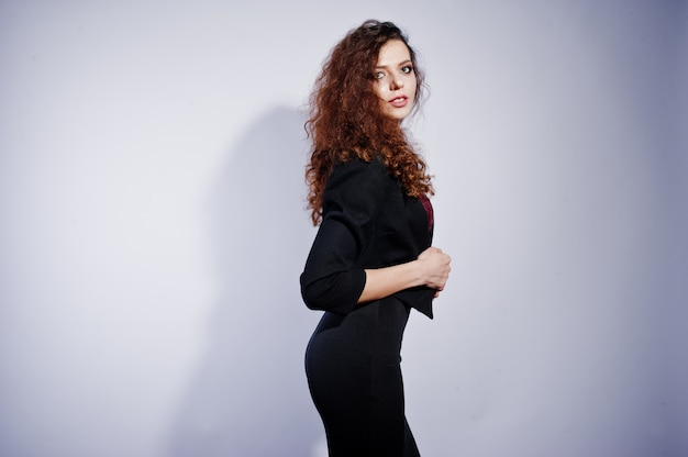 Brunette curly haired woman in black office jacket with skirt