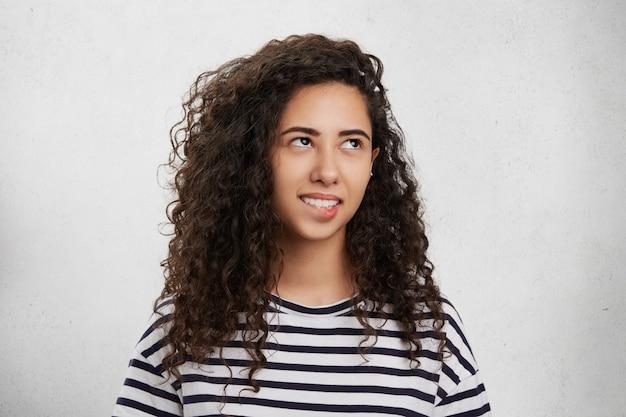 Кудрявая брюнетка женщина смешанной расы прикусила нижнюю губу как неуверенная и разочарованная, с задумчивым выражением лица