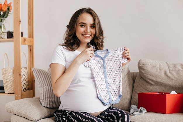 La donna incinta riccia castana esamina la parte anteriore e sorride