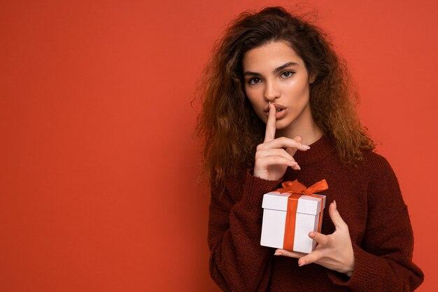Брюнетка кудрявая женщина изолирована на красном фоне стены в красном свитере