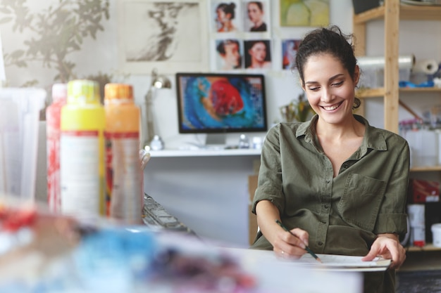 カジュアルな服装でブルネットのかわいい女性、嬉しい表情、鉛筆と空白の段ボールを持ち、インスピレーションと良い気分でスケッチをしながら、ワークショップや職場にいる