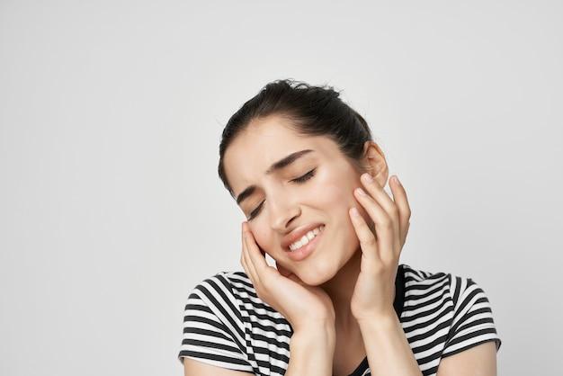 Brunette discomfort toothache dental treatment light background
