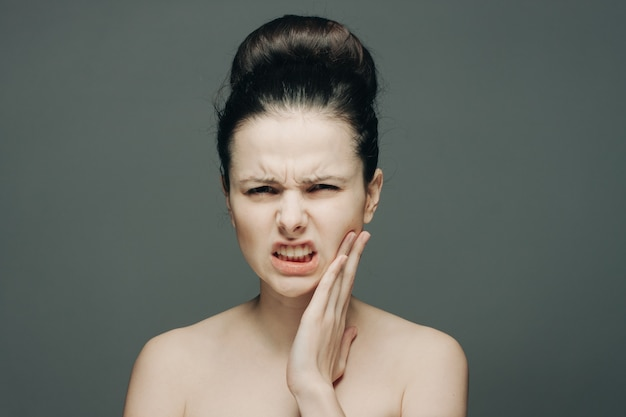 Brunette displeased expression holding hand on face gray background