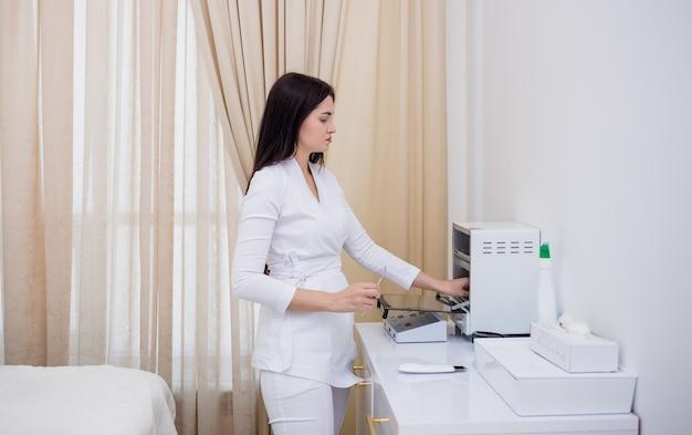 흰색 제복을 입은 갈색 머리 의사가 사무실의 살균 장치 근처에 서 있다