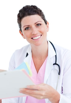 Brunette doctor reading paper and holding a stethoscope