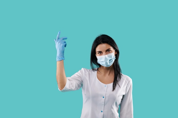 Brunette doctor wearing medical mask and latex gloves pointing her finger on blue background. isolated