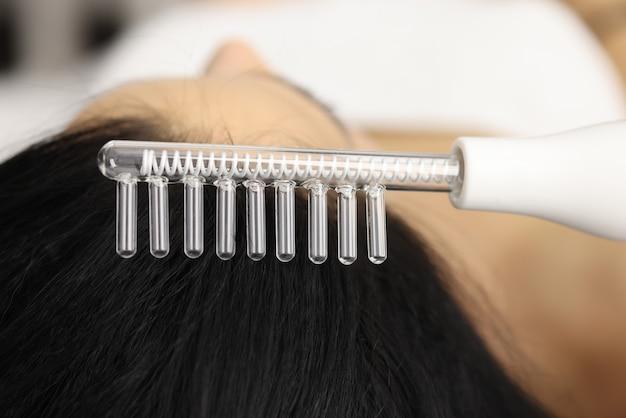 Брюнетка делает процедуры с расческой дарсонваль. концепция восстановления волосяных фолликулов