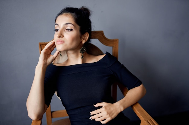 椅子の黒いドレスの暗い背景の近くでポーズをとるブルネットのイヤリングジュエリー。高品質の写真