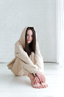 Брюнетка европейская девушка в спортивных штанах и толстовке с капюшоном сидит на белом деревянном полу в светлой комнате