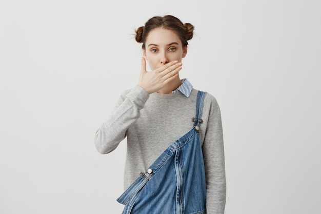 Brunette female 30s covering mouth with hand being quiet. confident woman in casual denim refusing from talking remaining silent. people, attitude concept