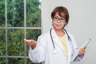 Brunette female doctor standing with clipboard near window in hospital