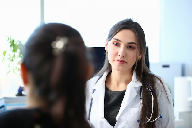 Brunette female doctor talking with patient