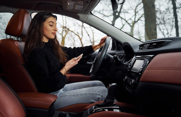 Brunette female driver sitting in modern car at daytime with smartphone.