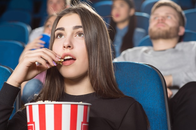 Brunette female eating popcorn while watching movies at the local movie theatre