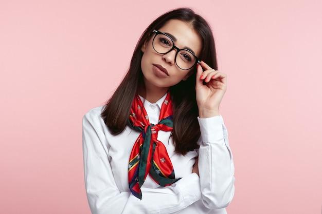 핑크에 고립 된 그녀의 안경을 들고 갈색 머리 여성