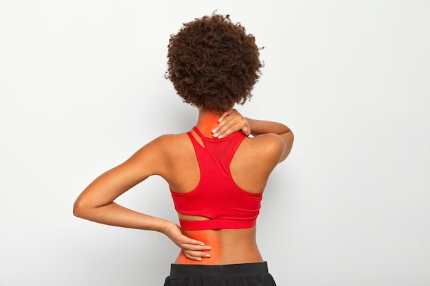 Brunette female model has joint pain in back and neck, has health problem, dressed in active wear isolated over white studio wall