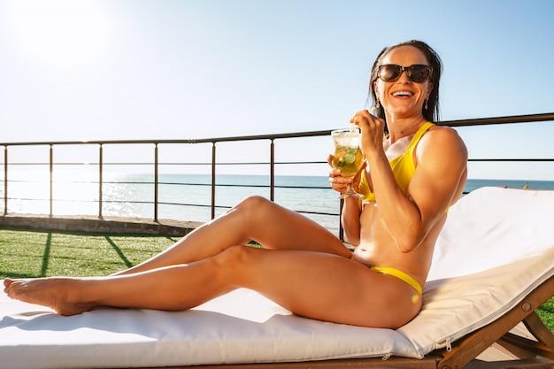 Брюнетка отдыхает на шезлонге в пляжном клубе