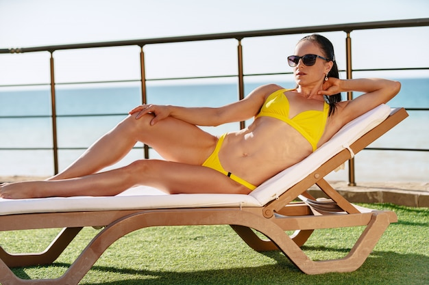 Brunette female relaxing on a sunbed in a beach club