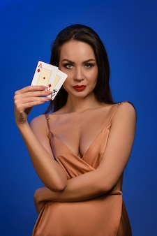 Brunette female in silk golden dress she is smiling showing two playing cards posing on blue wall