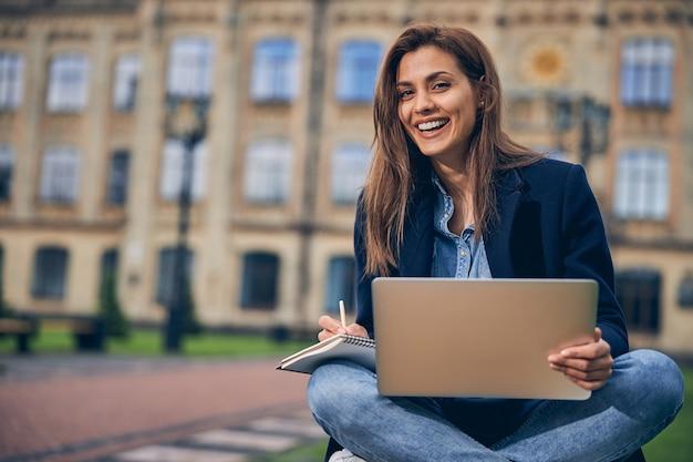 갈색 머리 여자 학생 다리를 건너와 노트북에서 작업하는 동안 웃 고 벤치에 앉아