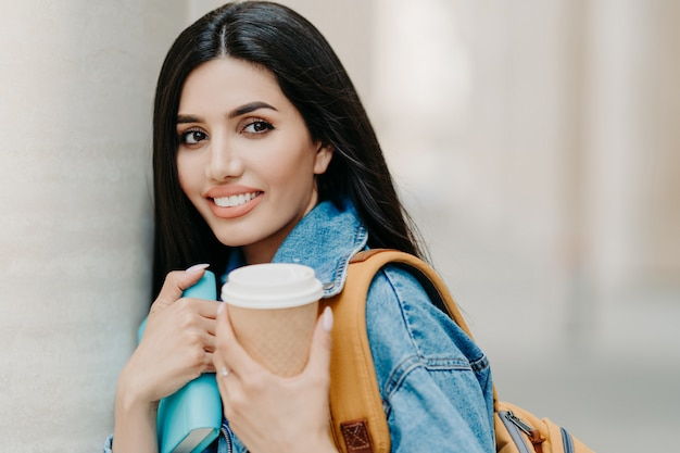 Brunette female student with makeup, dark long hair, dressed in denim jacket, holds takeaway coffee