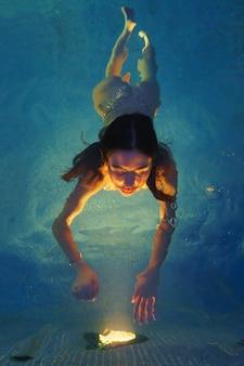 地熱水とスパプールで泳ぐブルネットの女性。美しい入浴者は、夜にプールランプから照らされたライトに彼女の手で手を差し伸べます。ハイアングルショット。顔にソフトセレクティブフォーカス。