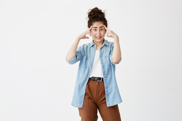 Brunette female with hair bun has headache after noisy party, clenches teeth and holds index fingers on temples. tired young female worker overworked after writing advertising content