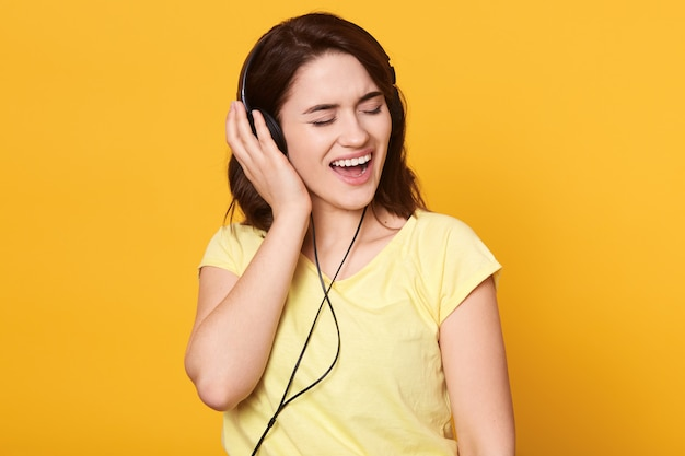 Brunette female with headphones listening to favorite music and singing