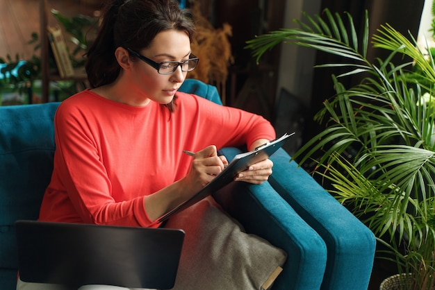 The brunette fills out the information in the questionnaire a woman works with documents does not