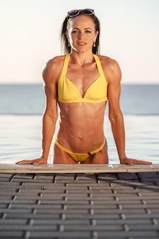 Brunette fitness model in yellow bikini coming out of pool