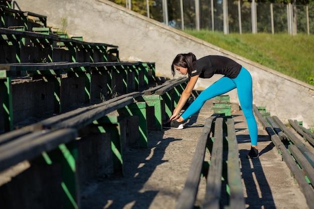 경기장에서 운동하기 전에 스트레칭을 하는 갈색 머리의 피트니스 여성. 태양 광선으로 야외 촬영입니다. 텍스트를 위한 공간