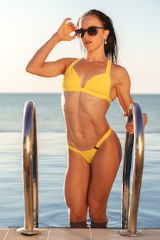 Brunette fitness woman in yellow bikini coming out of pool