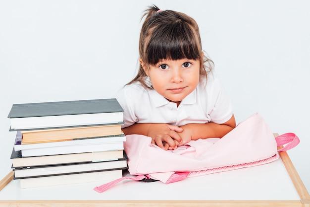 本とピンクのバックパックとテーブルの横にある椅子に座って、学校でブルネットの女の子