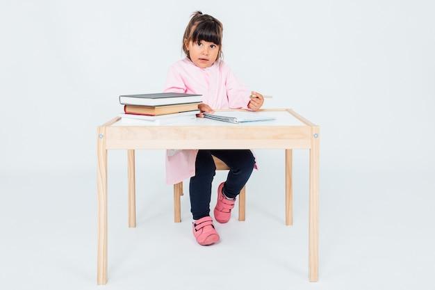 책상에 앉아 학교에서 갈색 머리 소녀