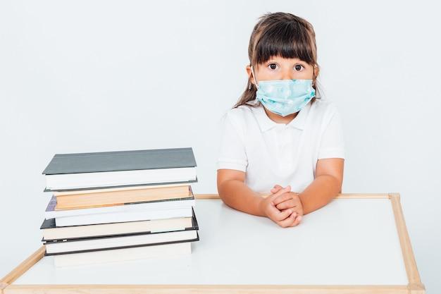 책상에 앉아 수술 마스크를 쓰고 학교에서 갈색 머리 소녀
