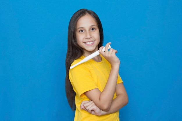 Brunette girl on a blue background smiling holds an electric toothbrush looking at the camera