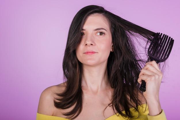 Brunette girl brushing her hair