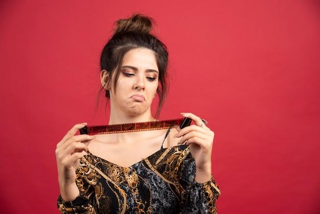 Девушка-брюнетка проверяет свою историю фотографий на поляроидной пленке и выглядит недовольной.