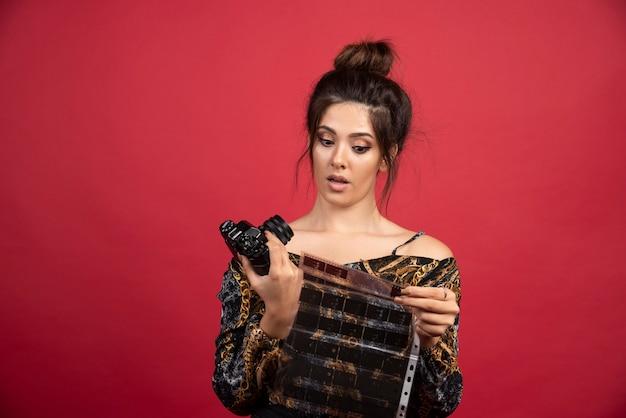 Brunette girl checks her photo history on polaroid film .