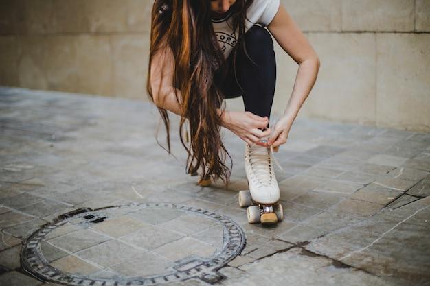 Brunette girl crouching tying rollerskates outside