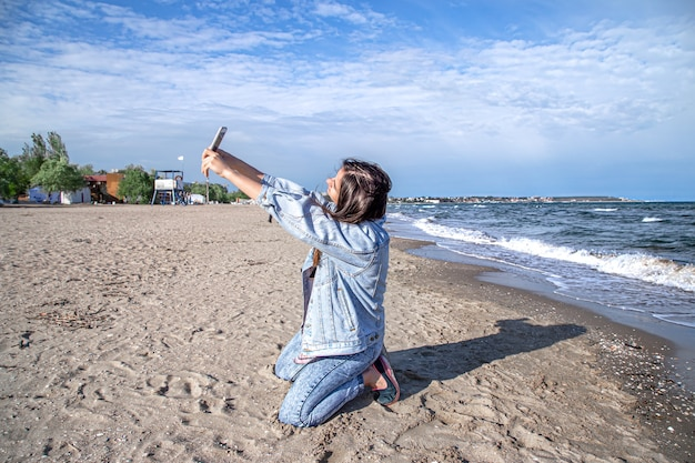 Brunette girl in a denim jacket takes a photo on the phone camera. the concept of travel and new experiences.