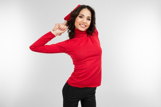Brunette girl doing warm-up stretching her back on a white studio background with copy space