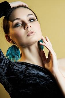 어깨가 열린 세련된 검은색 이브닝 드레스를 입은 갈색 머리 소녀, 귀에는 아름다운 큰 귀걸이가 있습니다. 완벽한 미소, 로맨틱한 여성의 이미지, 깨끗한 피부와 아름다운 메이크업