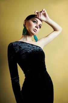 열린 어깨, 그녀의 귀에 아름다운 큰 귀걸이와 세련된 검은 이브닝 드레스를 입은 갈색 머리 소녀