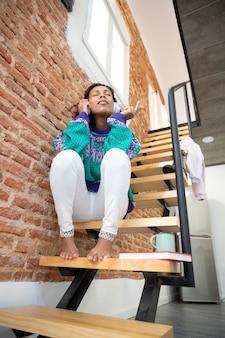 ヘッドフォンで音楽を楽しむブルネットの少女。彼女は家の階段に座っています。テキスト用のスペース。