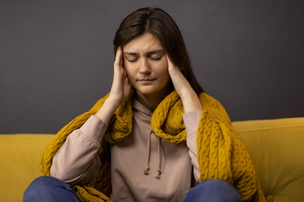 Brunette girl grabbing her head from headache with pain expression and a blanket on her shoulders Premium Photo
