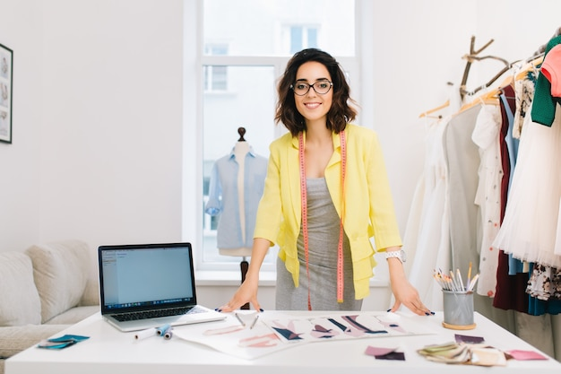 A brunette girl in a gray dress and yellow jacket is standing near the table in a workshop studio. she has a lot of creative stuff  on the table. she is smiling to the camera.