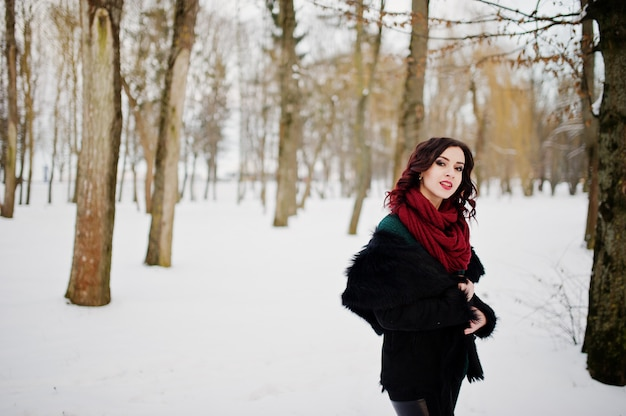 Brunette girl in green sweater, coat and red scarf outdoor on evening winter day.